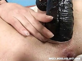 Dark haired babe gaped by a big black dildo
